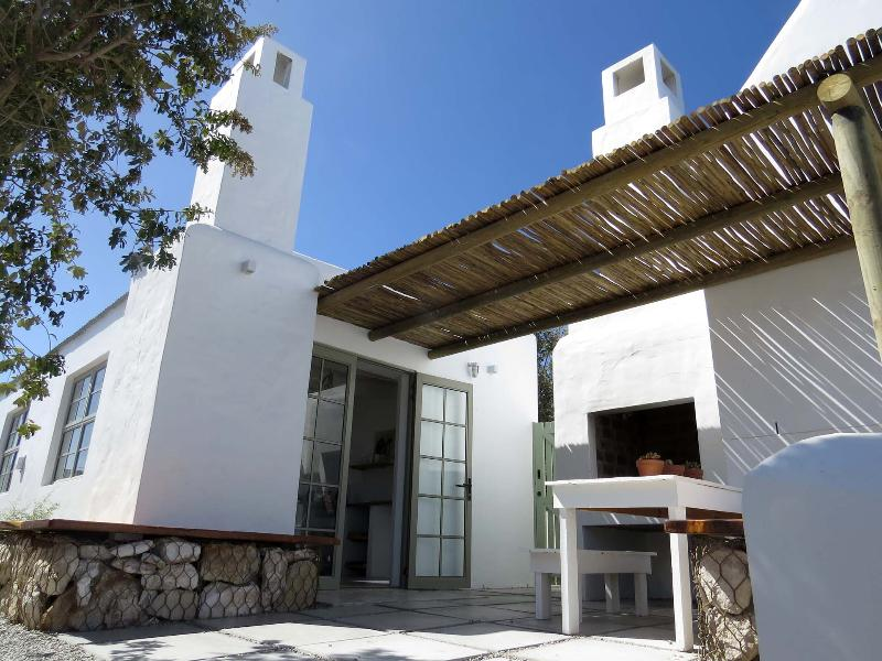 Patio, front door, entry gate and outdoor seating by the braai in local architectural style