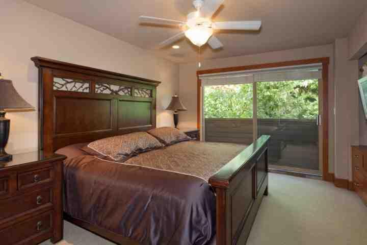 Una cama de matrimonio con la pared televisión y solarium
