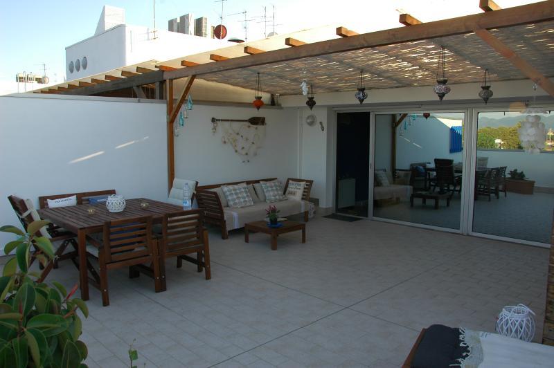 Terrazza arredata con divano, tavolo, 2 lettini