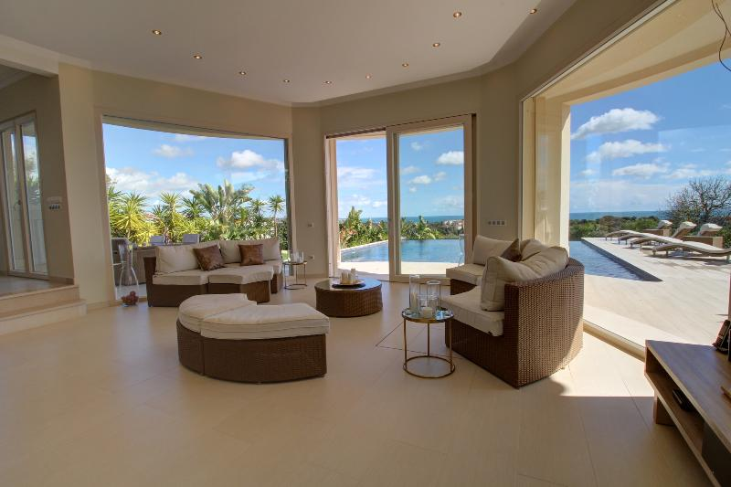 A view of the living room out to the pool and ocean.