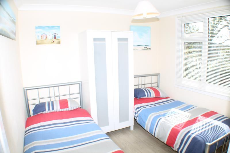 twin bedroom with wardrobe and chest of drawers