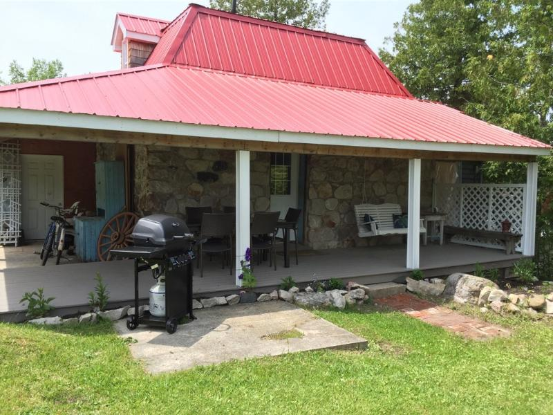 A BBQ and large dining table make the wrap around porch a wonderful spot for a meal.