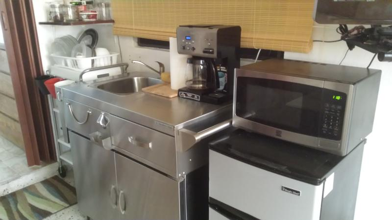 Mini kitchen area.  Furnished with a mini refrigerator, microwave oven, sink, coffee brewer as shown