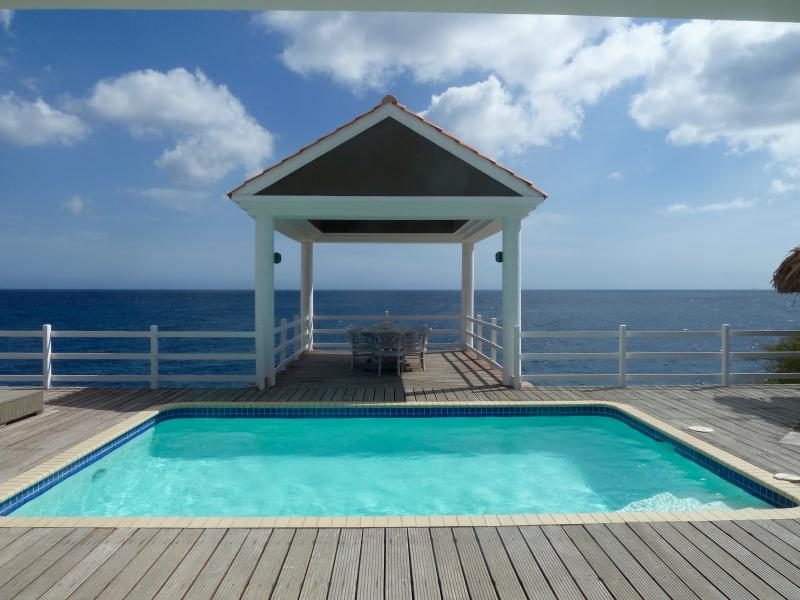 Pool deck with dining table right on the sea!