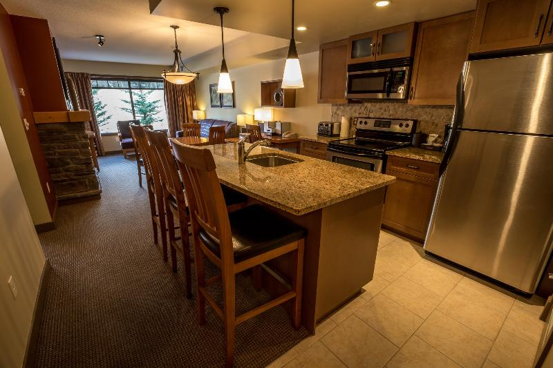 The open-plan kitchen features stainless steel appliances and a breakfast bar