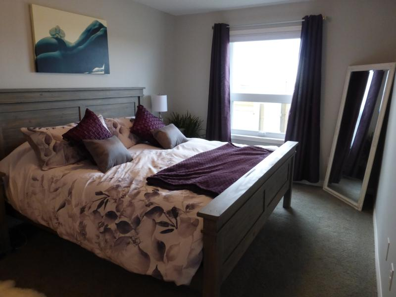 Master bedroom with King sized bed and luxurious linens.