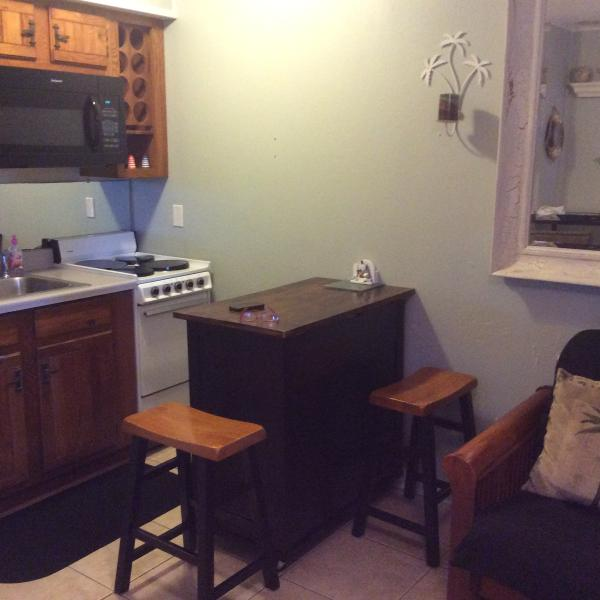 Kitchenette with small stove, sink, refrigerator, coffee maker, toaster, dishware, utensils
