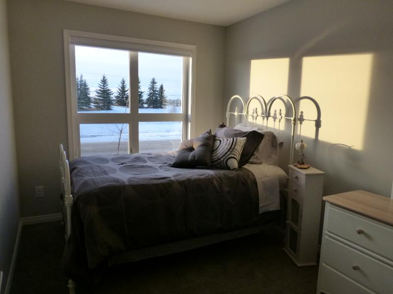 Comfortable double bed with delightful linens in the second bedroom.