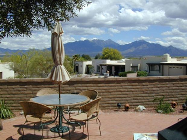 East facing patio with view of mountains. Lots of patio furniture and gas grill.
