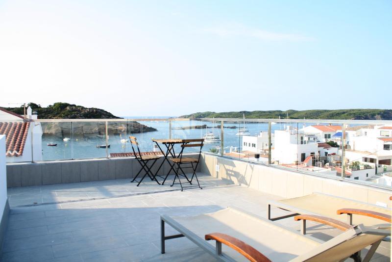 Terraza solarium en zona superior con 2 hamacas, mesita con sillas y ducha exterior.