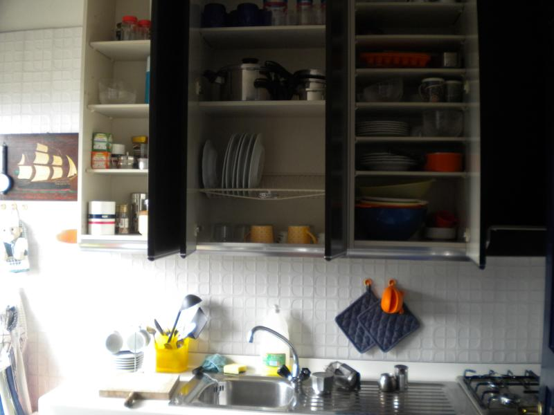 The shelf in the kitchen with pottery and pans