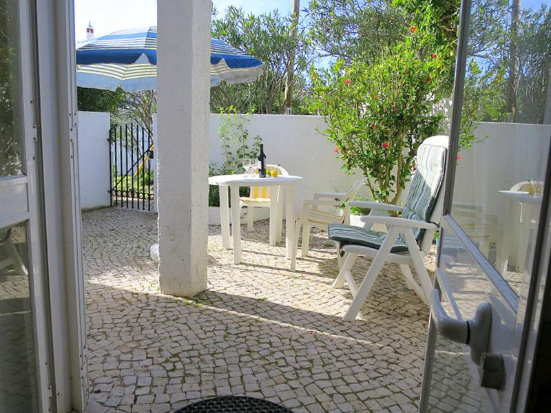 The rear garden patio backs onto a quiet grassy infill area and has a table and chairs and loungers