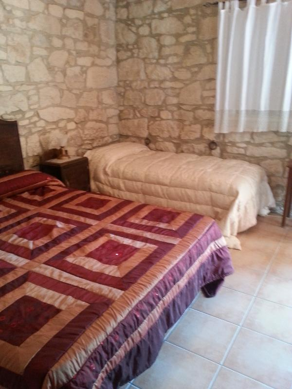camera molto luminosa con 2 lettini aggiunti , tutta in pietra, con soffitto in legno.