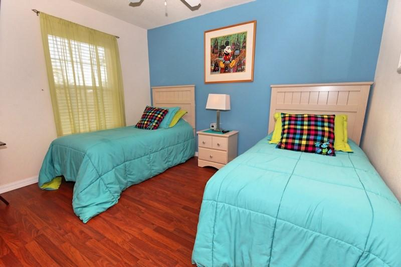 Two twin beds with Disney themed pictures and pillows.