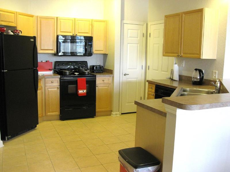 Fully equipped kitchen with laundry room off to side