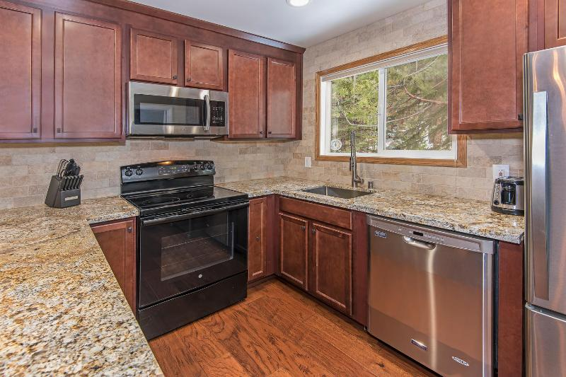 newly remodeled kitchen with gorgeous granite countertops. in unit washer and dryer next to kitchen