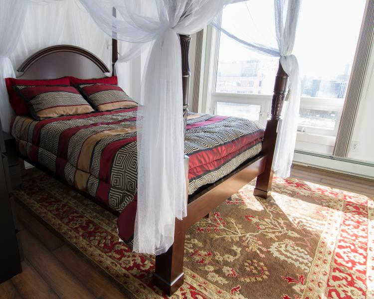 Grand Queen Canopy Bed in the bedroom with city view and sunset view