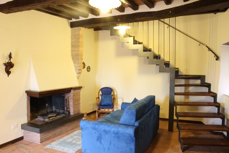 soggiorno con camineto e scala che sale al piano superiore