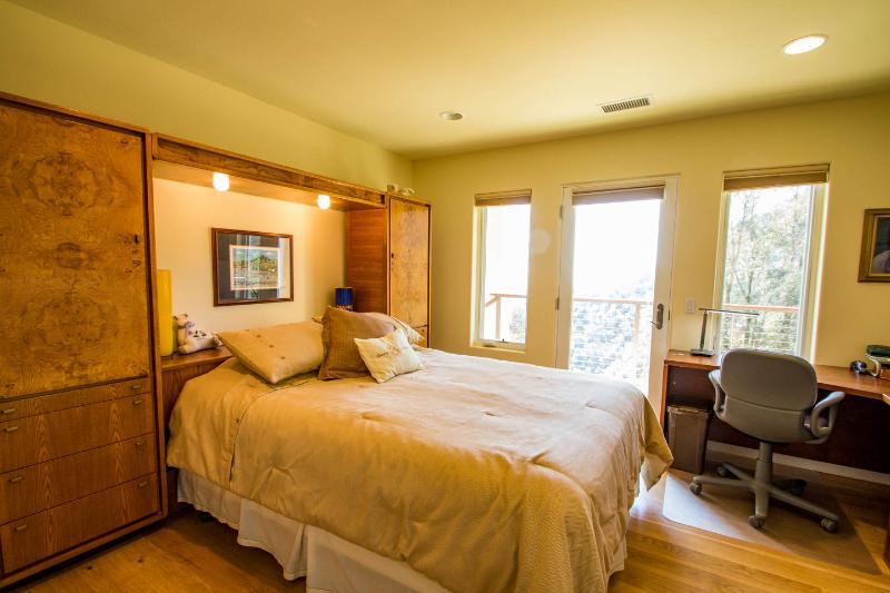 Guest bedroom with queen bed, smart TV & private door to pool & lower deck.