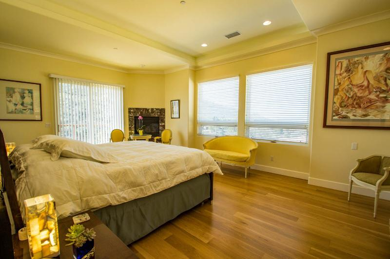 Master bed room with its own gas fireplace and west views of the sunset over the distant ocean.