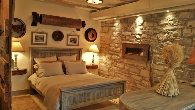 Queen size bed with memory foam mattress beside an exposed limestone wall with an electric fireplace