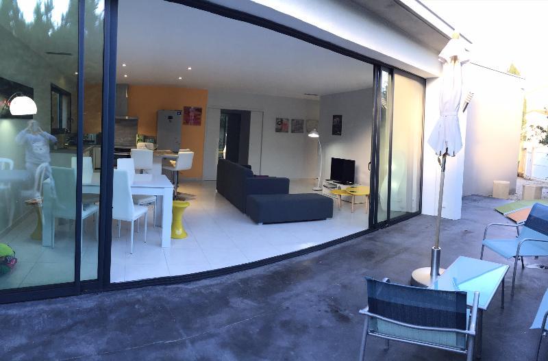 pièce à vivre et sa baie vitrée ouvrant sur terrasse et jardin