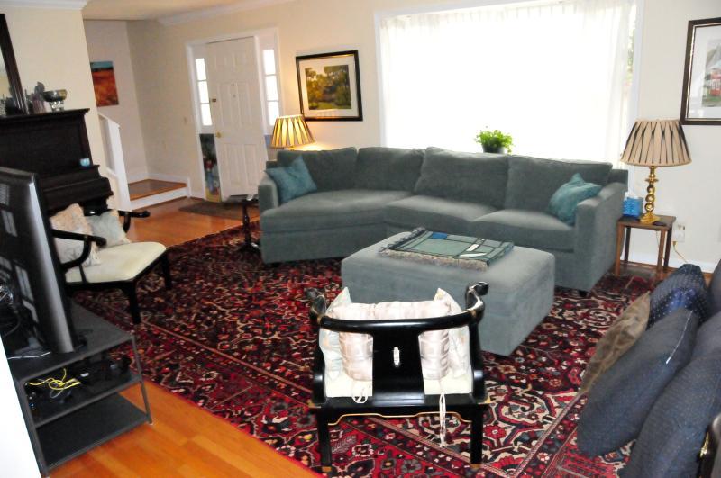 Amplia sala de estar con un cómodo sofá, enorme televisión, pantalla grande con cable / Amazon Stick, y el piano
