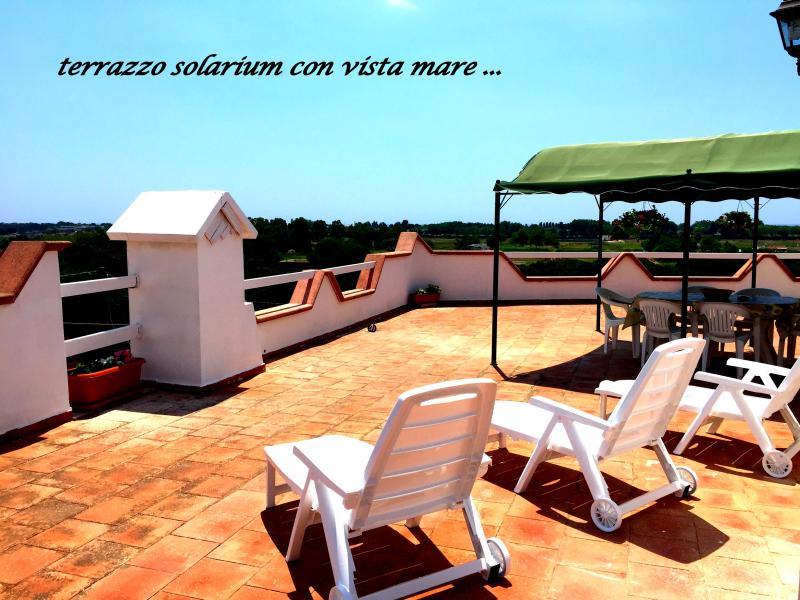 terrazzo solarium arredato con veranda ,tavolo sedie e lettini con  vista mare
