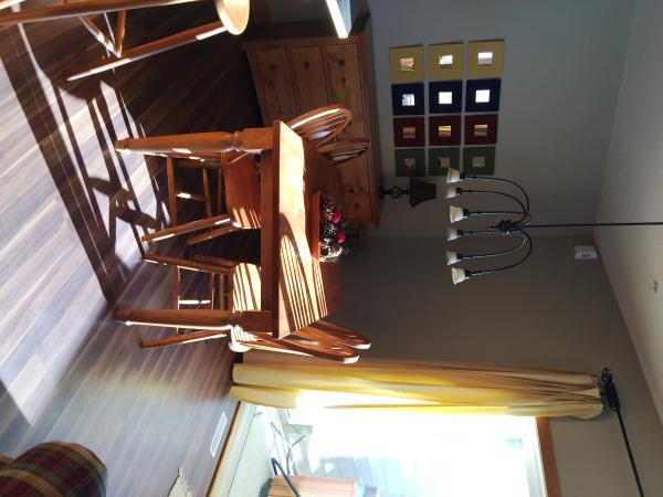 Sunny dining area with patio doors to deck with hot tub and BBQ