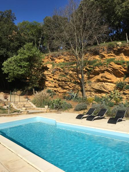 Our lovely swimming pool nestling under an impressive sandstone backdrop