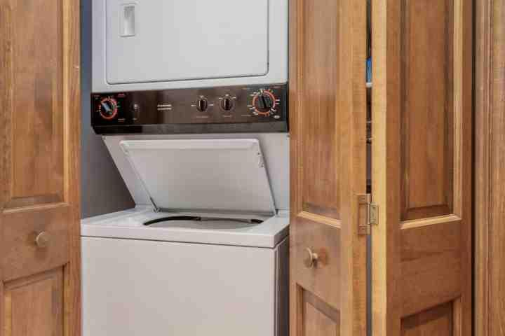 Full size stackable washer and dryer, located in the half bath near entry.