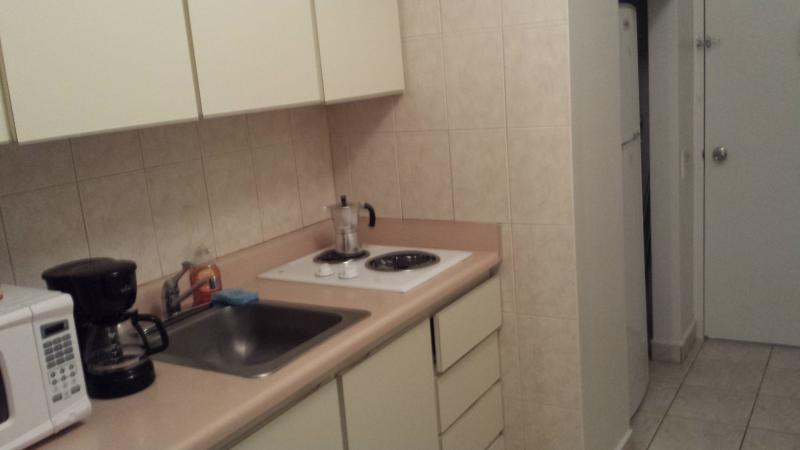 This is the kitchen. There is a microwave, refrigerator, utensils, coffee maker, cups and plates