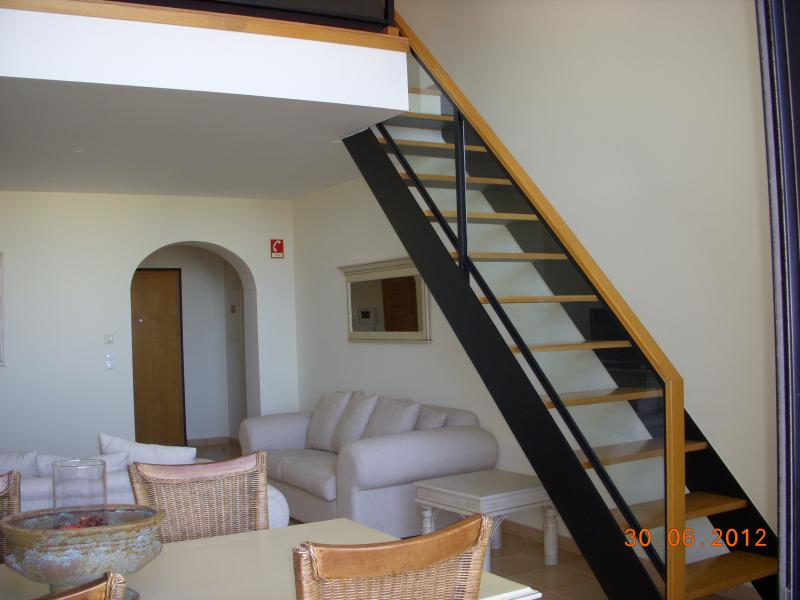 Living area with stairs to twin bedroom and ensuite bathroom.