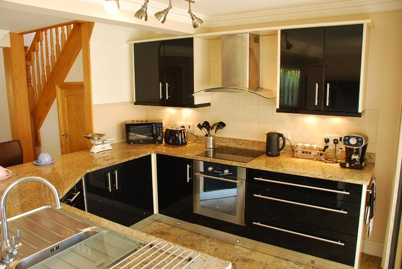 Well equipped modern kitchen with granite worktops, breakfast bar and two bar stools