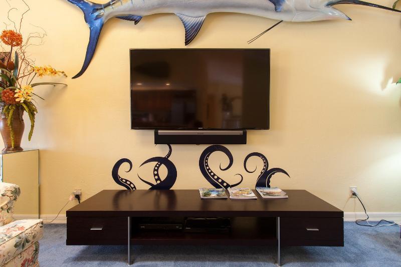 Habitación familiar de 65 pulgadas TV con un Marlin azul en la pared