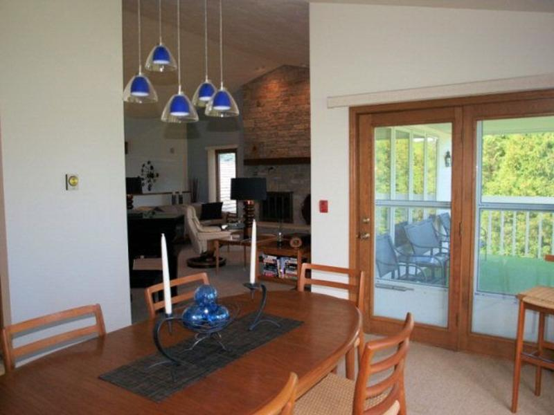 Looking from dining alcove into vaulted living area