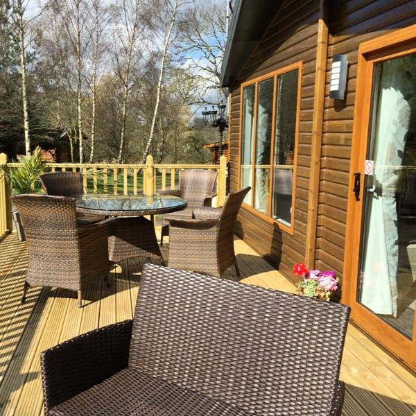 South facing lodge, front terrace with dining table and chairs.