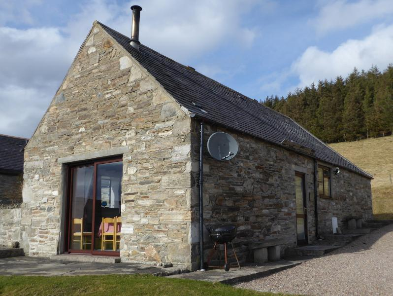 Glenlivet cottage with patio doors and entrance door on right. Cottage is south facing.