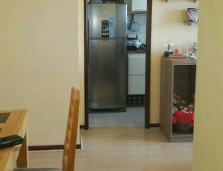 ao fundo geladeira duplex e parte da cozinha com prato, talheres, panela e utensílios necessários.
