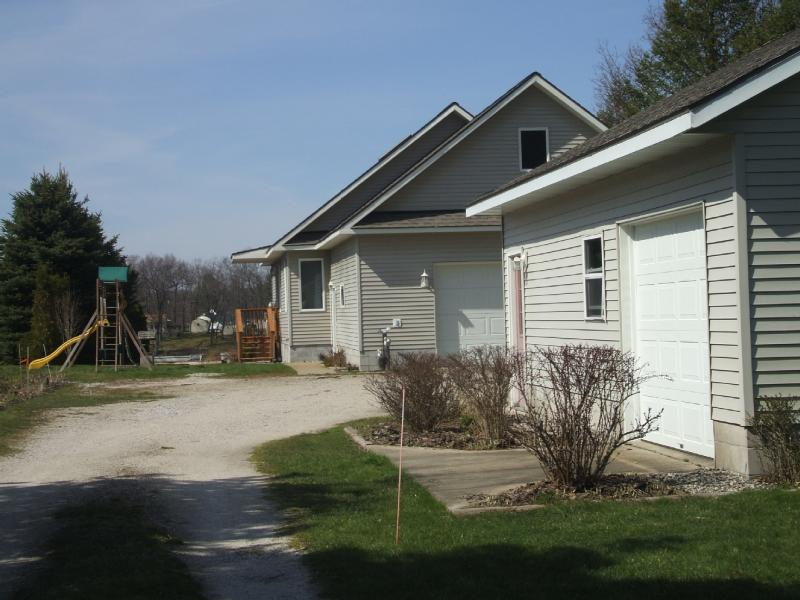 Back of the house. Swingset is straight ahead. The basketball net is between the two garages.