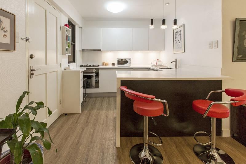 Fully equipped German designer kitchen, breakfast counter with red bar stools...