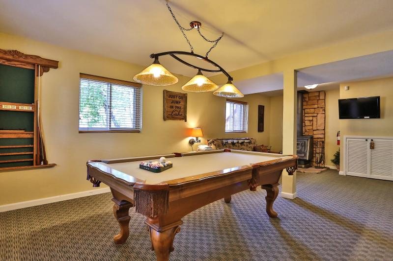 Large game room with pool table, Pac man machine, big screen TV and leather sleeper sofa.