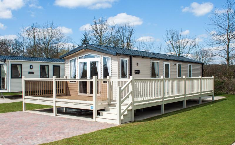 Luxury 2 bedroom caravan with decking and outside seating. Private parking bay.