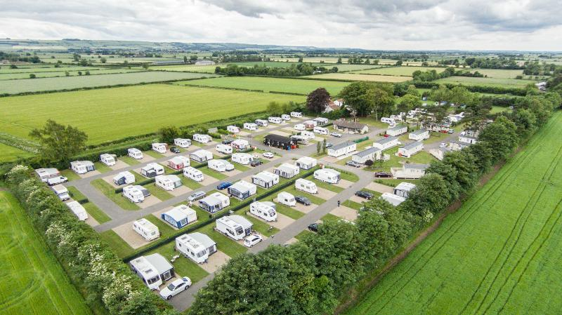 Aerial view of Jasmine Park. A mixture of holiday homes, touring caravans and tents.