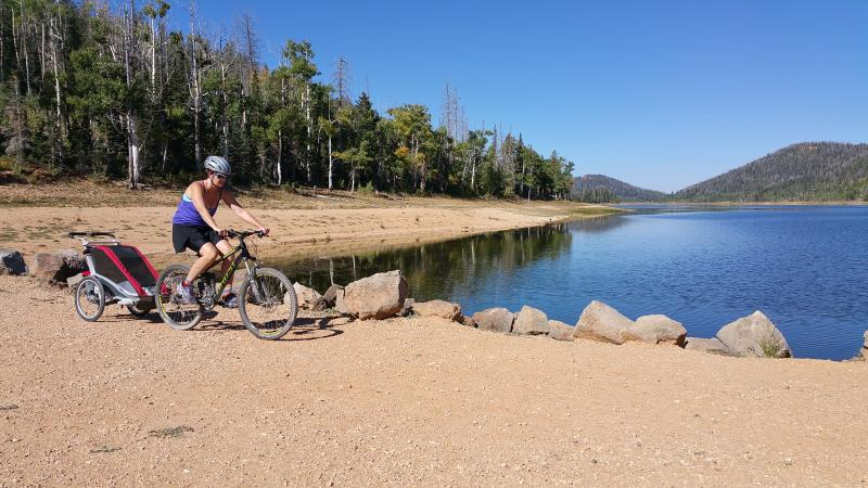 Me mountain biking with our toddler at Navajo Lake very close by