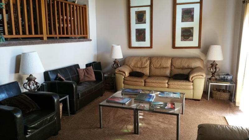 Living room: seats 10, cathedral ceiling, ceiling fan, tv/cable, bookshelf w/books, access to deck