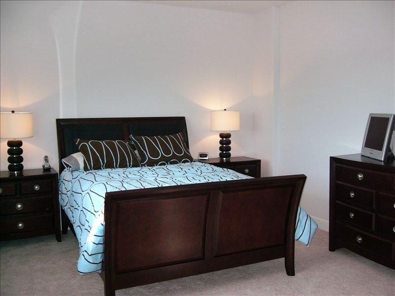 Queen Bed with walk in closet, bathroom, tub and shower.