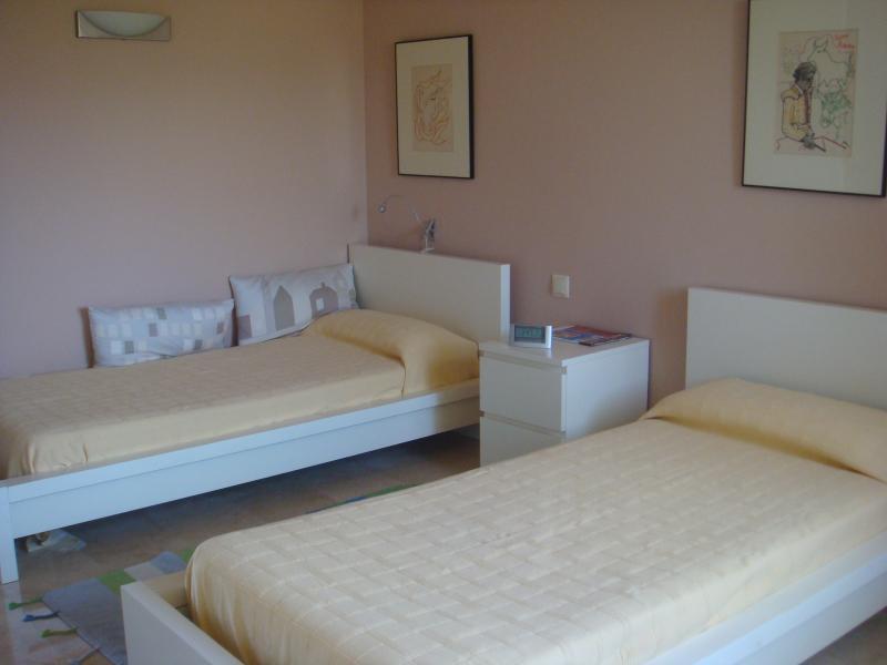 Dormitorio con dos camas, baño incluído y terraza