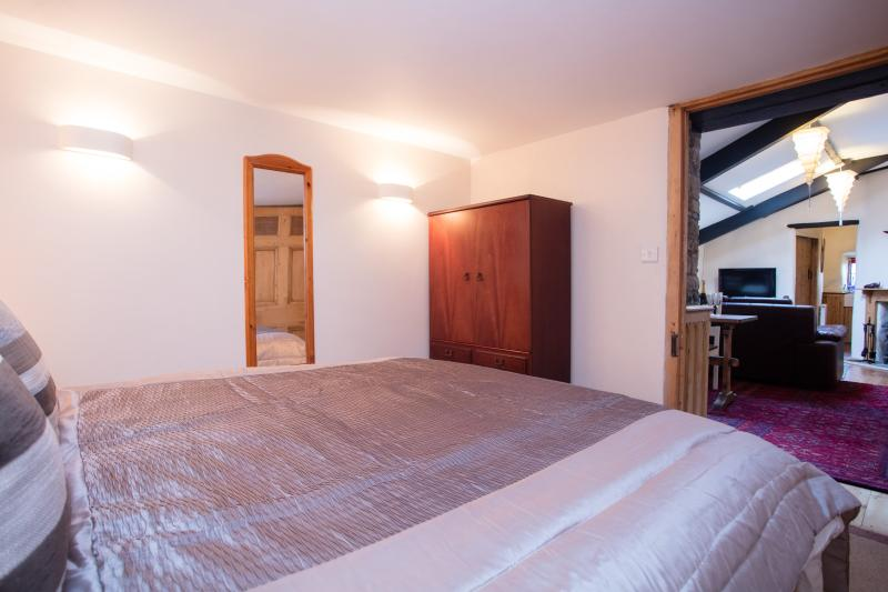Bedroom with Kingsize bed, small wardrobe & extra storage facility under the bed.