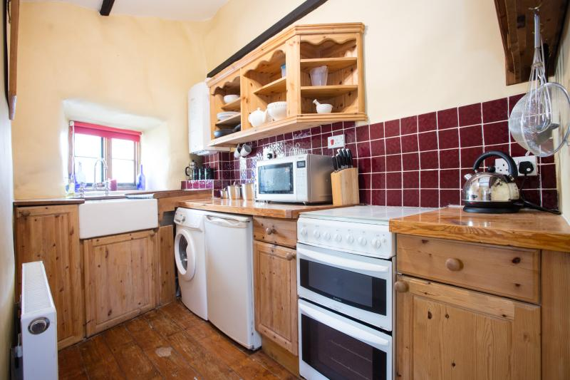 Small kitchen with gas cooker, microwave & washing machine.